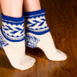 Stock Photo: Feet warm socks on dark wooden floor
