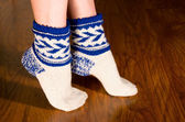 Feet warm socks on dark wooden floor — Stock Photo