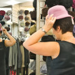 Woman trying on hat in the shop — Stock Photo #40551725