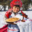 Shrovetide. Russiwomin sundress holding plate with pancakes — Stock Photo #40907477