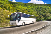Tourist bus traveling on road among mountains — Stock Photo