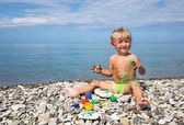 Kid soiled by paints on beach — Stock Photo