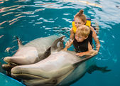 Mum with kid floats with dolphins in pool — Stock Photo