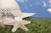 Beach hat with starfish on grass — Stock Photo