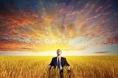 Muž sedící na poli — Stock fotografie