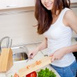 Smiling woman preparing fresh salad - Stock Photo
