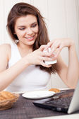 Happy woman enjoying tea and cookies — Stock Photo