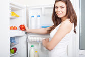 Woman taking pepper from fridge — Stock Photo
