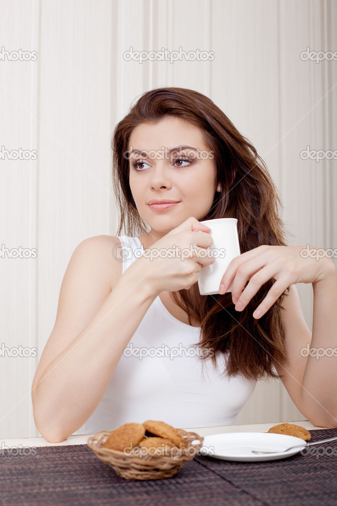 Beautiful woman seated at her desk and enjoying tea and cookies, looking to the right — Stock Photo #13183291