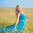 Beautiful woman wearing blue dress on a field — Stock Photo