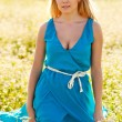 Beautiful woman wearing blue dress on a field — Stock Photo #13489415
