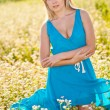 Smiling woman wearing blue dress on a field - Stock Photo