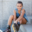 Smiling girl sitting on the stairs and puts on skates - Photo
