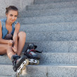 Girl sitting on the stairs and puts on skates - Photo