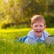 Laughing boy laying on grass in the park with laptop — Zdjęcie stockowe