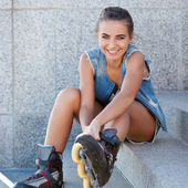 Smiling girl sitting on the stairs and puts on skates — Stockfoto