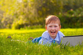 Laughing boy laying on grass in the park with laptop — Stock Photo