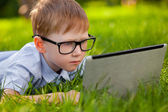 Boy laying on grass in the park with laptop — Stock Photo