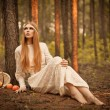 Woman sitting on  ground in the forest - Stock Photo