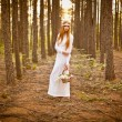 Beautiful woman standing in forest - Stock Photo