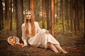 Woman sitting on ground in the forest — Stock Photo