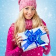 Woman wearing knitwear holding giftbox — Stock Photo #14278283