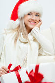 Happy woman in santa hat sitting near sofa — Stock Photo