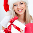 Happy woman in santa hat holding gift boxes — Stockfoto