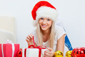 Woman in santa hat laying on the carpet — Stock Photo