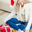 Woman wearing santa hat sitting on the floor — Stock Photo