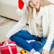 Stock Photo: Woman wearing santa hat sitting on the floor