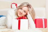 Frau verlegung auf dem boden mit geschenken — Stockfoto