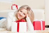 Glückliche frau verlegung auf dem boden mit geschenken — Stockfoto