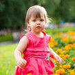 Little girl in orange flowers — Stock Photo
