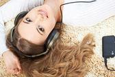 Femme allongée sur le tapis et écouter de la musique — Photo
