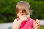 Little girl smelling flower — Stock Photo