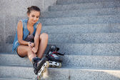 Girl sitting on the stairs and puts on skates — Stock Photo