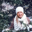 Happy woman under snowfall - Stock Photo