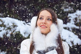 Beautiful brunette woman standing under snowfall — Stock Photo