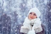 Beautiful woman walking outdoors under snowfall — Stock Photo