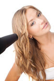 Blonde woman holding hairdryer — Stock Photo
