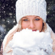 Woman holding snow on hands — Stock Photo #18912249