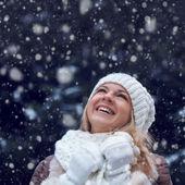 Happy woman under snowfall — Stock Photo