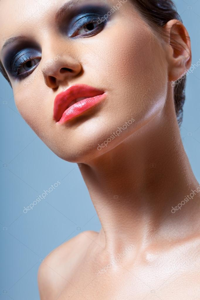 Brunette  woman face closeup portrait with smoky eyes makeup over blue backgound — Stock Photo #18912331