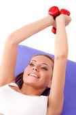 Kobieta na podłodze i zniesienie dumbbells — Zdjęcie stockowe