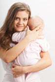 Young mother holding her baby girl on hands — Stock Photo