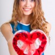 Young woman holding heart shaped box — Stockfoto