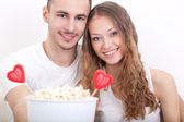 Young couple sitting with popcorn — Stock Photo