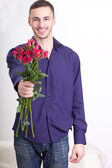 Young man giving flowers — Stock Photo