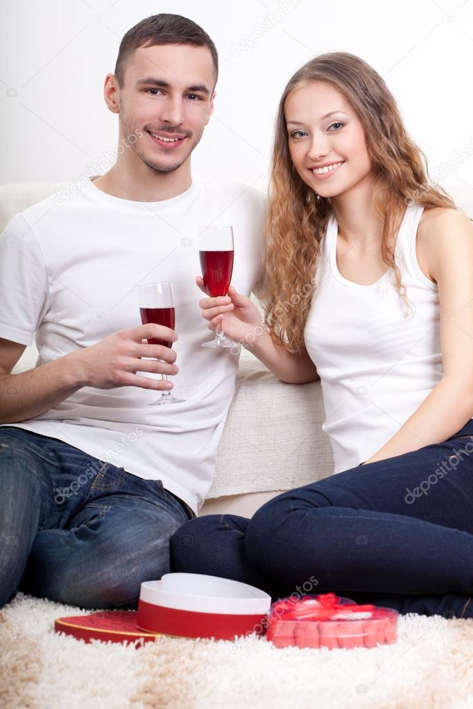 Happy young couple  holding glasses with wine at home on floor — Stock Photo #19413335